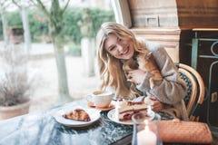 Όμορφη νέα γυναίκα με την ξανθή μακρυμάλλη συνεδρίαση με την αναμμένη Στοκ Εικόνες