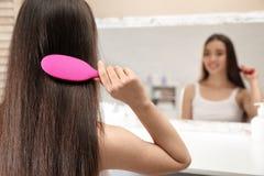 Όμορφη νέα γυναίκα με τη βούρτσα τρίχας που εξετάζει τον καθρέφτη στοκ εικόνες