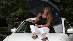 Όμορφη νέα γυναίκα με τη μακροχρόνια ξανθή συνεδρίαση τρίχας στην κουκούλα του άσπρου αυτοκινήτου με την ομπρέλα στη βροχερή θερι απόθεμα βίντεο