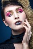 Όμορφη νέα γυναίκα με τη μόδα makeup στο μπλε Στοκ Φωτογραφία
