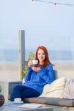 Όμορφη νέα γυναίκα με τη συνεδρίαση φλιτζανιών του καφέ στον καφέ επάνω Στοκ Εικόνα
