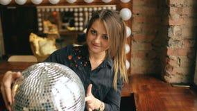 Όμορφη νέα γυναίκα με τη σφαίρα disco που θέτει και που χαμογελά στο στούντιο στο εσωτερικό φιλμ μικρού μήκους