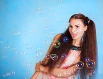 Όμορφη νέα γυναίκα με τις φυσαλίδες σαπουνιών Στοκ Εικόνα