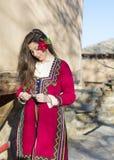Όμορφη νέα γυναίκα με το βαλκανικό λαϊκό κόκκινο κοστούμι Στοκ Φωτογραφίες