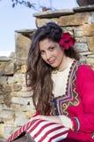 Όμορφη νέα γυναίκα με το βαλκανικό λαϊκό κόκκινο κοστούμι Στοκ φωτογραφία με δικαίωμα ελεύθερης χρήσης