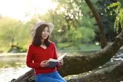 Όμορφη νέα γυναίκα με το βιβλίο ανάγνωσης χαμόγελου στο πάρκο και συνεδρίαση σε ένα ξύλινο δέντρο Στοκ Εικόνες