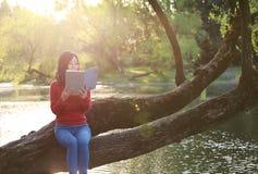 Όμορφη νέα γυναίκα με το βιβλίο ανάγνωσης χαμόγελου στο πάρκο και συνεδρίαση σε ένα ξύλινο δέντρο Στοκ φωτογραφίες με δικαίωμα ελεύθερης χρήσης