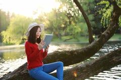 Όμορφη νέα γυναίκα με το βιβλίο ανάγνωσης χαμόγελου στο πάρκο και συνεδρίαση σε ένα ξύλινο δέντρο στον ποταμό Στοκ Φωτογραφία
