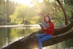 Όμορφη νέα γυναίκα με το βιβλίο ανάγνωσης χαμόγελου στο πάρκο και συνεδρίαση σε ένα ξύλινο δέντρο στον ποταμό Στοκ Εικόνες