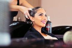 Όμορφη νέα γυναίκα με το κεφάλι πλύσης κομμωτών στο κομμωτήριο Στοκ εικόνα με δικαίωμα ελεύθερης χρήσης