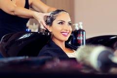 Όμορφη νέα γυναίκα με το κεφάλι πλύσης κομμωτών στο κομμωτήριο Στοκ Εικόνες