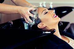 Όμορφη νέα γυναίκα με το κεφάλι πλύσης κομμωτών στο κομμωτήριο Στοκ Φωτογραφίες