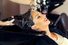 Όμορφη νέα γυναίκα με το κεφάλι πλύσης κομμωτών στο κομμωτήριο Στοκ Φωτογραφία