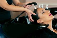 Όμορφη νέα γυναίκα με το κεφάλι πλύσης κομμωτών στο κομμωτήριο Στοκ Εικόνα
