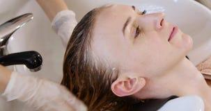 Όμορφη νέα γυναίκα με το κεφάλι πλύσης κομμωτών στο κομμωτήριο φιλμ μικρού μήκους