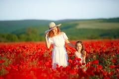 Όμορφη νέα γυναίκα με το κορίτσι παιδιών στον τομέα παπαρουνών ευτυχής οικογένεια που έχει τη διασκέδαση στη φύση υπαίθριο πορτρέ στοκ φωτογραφία