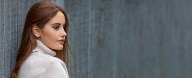 Όμορφη νέα γυναίκα με το κόκκινο πανοραμικό έμβλημα τρίχας στοκ εικόνα με δικαίωμα ελεύθερης χρήσης