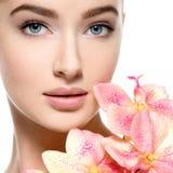 Όμορφη νέα γυναίκα με το λουλούδι διαθέσιμο πλησίον στο πρόσωπο στοκ φωτογραφία