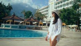 Όμορφη νέα γυναίκα με το μακρυμάλλες περπάτημα κοντά στην πισίνα Τουρίστας στον ήλιο, διακοπές φιλμ μικρού μήκους