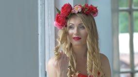 Όμορφη νέα γυναίκα με το στεφάνι των κόκκινων λουλουδιών φιλμ μικρού μήκους