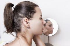 Όμορφη νέα γυναίκα μπροστά από το στρογγυλό καθρέφτη Ελκυστικό κορίτσι που κάνει makeup στο σπίτι Στοκ φωτογραφίες με δικαίωμα ελεύθερης χρήσης