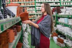 Όμορφη νέα γυναίκα πελατών που κρατά ένα δοχείο λουλουδιών Στοκ Φωτογραφίες