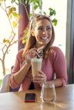 Όμορφη νέα γυναίκα που έχει ένα κενό σε έναν καφέ μια ηλιόλουστη ημέρα στοκ φωτογραφία