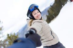 Όμορφη νέα γυναίκα που έχει τη διασκέδαση πέρα από το χειμερινό υπόβαθρο Στοκ Εικόνες