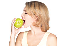 Όμορφη νέα γυναίκα που δαγκώνει το δάγκωμα ένα φρέσκο ώριμο μήλο Στοκ Εικόνες