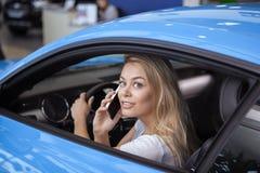Όμορφη νέα γυναίκα που αγοράζει το νέο αυτοκίνητο στον αντιπρόσωπο στοκ φωτογραφία