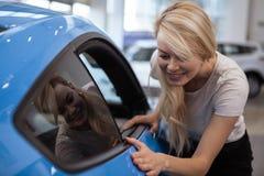 Όμορφη νέα γυναίκα που αγοράζει το νέο αυτοκίνητο στον αντιπρόσωπο στοκ φωτογραφίες