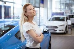 Όμορφη νέα γυναίκα που αγοράζει το νέο αυτοκίνητο στον αντιπρόσωπο στοκ φωτογραφίες με δικαίωμα ελεύθερης χρήσης