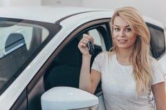 Όμορφη νέα γυναίκα που αγοράζει το νέο αυτοκίνητο στον αντιπρόσωπο στοκ εικόνα με δικαίωμα ελεύθερης χρήσης