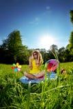 Όμορφη νέα γυναίκα που ακούει τη μουσική στο πάρκο Στοκ Φωτογραφία
