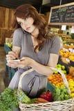 Όμορφη νέα γυναίκα που ακούει το κινητό τηλέφωνο κάνοντας μια σημείωση του καταλόγου αγορών στην αγορά Στοκ Εικόνες