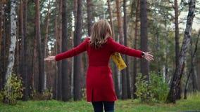 Όμορφη νέα γυναίκα που απολαμβάνει τη θερμή ημέρα φθινοπώρου και μια περιστροφή διασκέδασης στο δάσος φθινοπώρου σε αργή κίνηση απόθεμα βίντεο