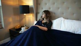 Όμορφη νέα γυναίκα που βάζει σε ένα κρεβάτι στο σπίτι, που φαίνεται έξω το παράθυρο απόθεμα βίντεο