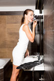 Όμορφη νέα γυναίκα που βάζει στο makeup στο λουτρό Στοκ εικόνες με δικαίωμα ελεύθερης χρήσης