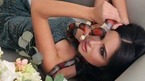 Όμορφη νέα γυναίκα που βρίσκεται σε έναν καναπέ με το φίδι φιλμ μικρού μήκους