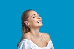 Όμορφη νέα γυναίκα που γελά στο μπλε υπόβαθρο Στοκ εικόνα με δικαίωμα ελεύθερης χρήσης