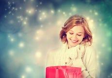 Όμορφη νέα γυναίκα που εξετάζει μια τσάντα δώρων Στοκ Εικόνες