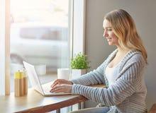 Όμορφη νέα γυναίκα που εργάζεται με τον υπολογιστή στον καφέ Δακτυλογράφηση σε ένα πληκτρολόγιο Στοκ Φωτογραφίες