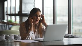 Όμορφη νέα γυναίκα που εργάζεται με το lap-top και που μιλά στο smartphone που μιλά στη συνεδρίαση πελατών κοντά στο παράθυρο απόθεμα βίντεο