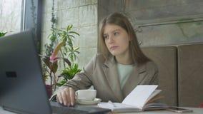 Όμορφη νέα γυναίκα που εργάζεται με το lap-top στον καφέ και τον καφέ κατανάλωσης απόθεμα βίντεο