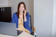 Όμορφη νέα γυναίκα που εργάζεται στον υπολογιστή και που μιλά στο τηλέφωνο στοκ φωτογραφία με δικαίωμα ελεύθερης χρήσης