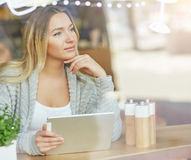 Όμορφη νέα γυναίκα που εργάζεται στο lap-top και ονειρεμένα που φαίνεται έξω το παράθυρο μέσω του γυαλιού Στοκ φωτογραφία με δικαίωμα ελεύθερης χρήσης