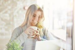 Όμορφη νέα γυναίκα που εργάζεται στο lap-top και που κρατά ένα φλυτζάνι του ποτού μέσω του γυαλιού Στοκ Εικόνα
