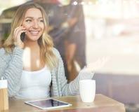 Όμορφη νέα γυναίκα που εργάζεται στο lap-top και που μιλά στο τηλέφωνο μέσω του γυαλιού Στοκ φωτογραφία με δικαίωμα ελεύθερης χρήσης