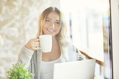 Όμορφη νέα γυναίκα που εργάζεται στο lap-top, που κρατά ένα φλυτζάνι του ποτού και που εξετάζει τη κάμερα μέσω του γυαλιού Στοκ εικόνα με δικαίωμα ελεύθερης χρήσης