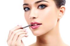 Όμορφη νέα γυναίκα που εφαρμόζει τα χείλια makeup με την καλλυντική βούρτσα στοκ εικόνα